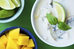 Thailändsk Tom Kha Gai soppa med mango och limefrukt på den gröna tabellen Fotografering för Bildbyråer