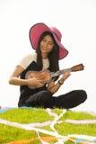 Thailändsk ung flicka med ukulelet på kullen royaltyfri foto