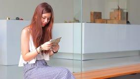 Thailändsk vuxen härlig flicka som använder hennes smarta telefon och leende