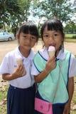 Thailändska barn i studentlikformig äter glass arkivfoto