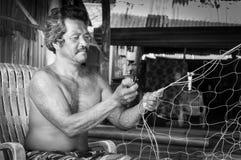 Thailändska fiskare som lagar hans fisknät i Thailand Royaltyfri Fotografi
