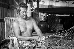 Thailändska fiskare som lagar hans fisknät i Thailand Arkivbild