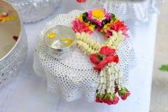 Thailändska girlandblommor och vatten med jasmin och rosblomkronan i bunke på det guld- magasinet Royaltyfria Bilder