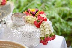 Thailändska girlandblommor och vatten med jasmin och rosblomkronan i bunke på det guld- magasinet Royaltyfri Foto
