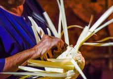 Thailändska hantverk - väva en hatt av thailändska kvinnor, naturliga ingredienser i thailändsk turismfestival i natten royaltyfria bilder