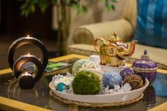 Thailändska inre detaljer av brunnsorten, stearinljus på tabellen och kokkärl med te arkivfoton