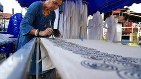 Thailändska kvinnor skapar och danandebatikmålarfärg och drar på tyg stock video