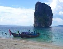 Thailändska longtailfartyg på kristallklart grönt turkosvatten av berömd tropisk vit sand sätter på land på Krabi, det Andaman ha royaltyfri bild