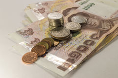 Thailändska pengar, 1000 bahtsedlar och mynt på vit bakgrund Fotografering för Bildbyråer