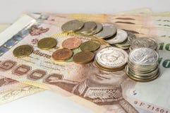 Thailändska pengar, 1000 bahtsedlar och mynt på vit bakgrund Royaltyfri Fotografi