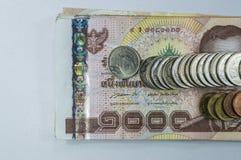 Thailändska pengar, 1000 bahtsedlar och mynt på vit bakgrund Royaltyfria Foton