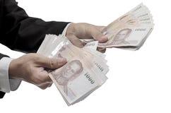 Thailändska pengar i handen, inklusive snabb bana Arkivfoto