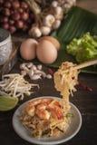 Thailändska stekte nudlar eller blockthai med räka på den vita plattan som förläggas på trätabellen där, är ägg, vitlök, böngrodd arkivbild