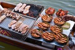 Thailändska traditionella bevattnar marknadsför fartyget som säljer ny tioarmad bläckfisk och praw Royaltyfri Fotografi