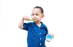 Thailändskt behandla som ett barn pojken som borstar tänder I behandla som ett barn handinnehavkoppen Royaltyfria Foton