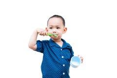 Thailändskt behandla som ett barn pojken som borstar tänder I behandla som ett barn handinnehavkoppen Royaltyfri Fotografi