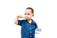 Thailändskt behandla som ett barn pojken som borstar tänder I behandla som ett barn handinnehavkoppen Royaltyfria Bilder