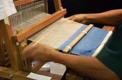 Thailändskt folk som använder den lilla vävstolen eller väver maskinen för att väva show Arkivfoton