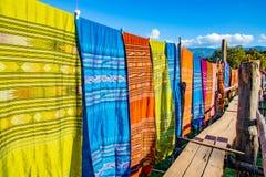 Thailändskt kulturellt bomullstyg som hänger längs träbron royaltyfri fotografi