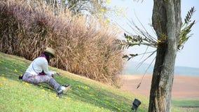 Thailändskt kvinnasammanträde på jordningen i trädgården på Chiangrai, Thailand lager videofilmer