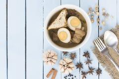 Thailändskt matKai-PA-lo med kryddor och kitchenware på trähimmelblått Arkivbild