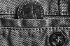 Thailändskt mynt med en valör av baht 10 i facket av grov bomullstvilljeans med knappen, monokromskott Arkivfoto
