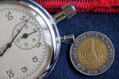 Thailändskt mynt med en valör av 10 baht och stoppur på gammalt slitet mörker - jeans med den röda bandbakgrunden - affärsbakgrun Arkivfoto