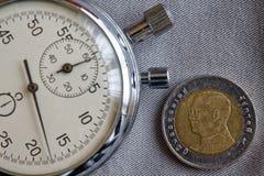 Thailändskt mynt med en valör av baht 10 (tillbaka sida) och stoppuren på den gråa grov bomullstvillbakgrunden - affärsbakgrund Royaltyfri Fotografi