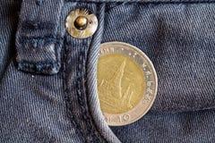 Thailändskt mynt med en valör av baht tio i facket av föråldrad blå grov bomullstvilljeans Arkivfoto