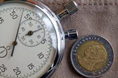 Thailändskt mynt med en valör av baht tio (tillbaka sida) och stoppuren på den beigea grov bomullstvillbakgrunden - affärsbakgrun Royaltyfri Bild