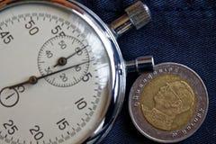 Thailändskt mynt med en valör av baht tio (tillbaka sida) och stoppuren på mörker - jeansbakgrund - affärsbakgrund Royaltyfri Foto