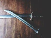 Thailändskt svärd på trätabellen Arkivfoto