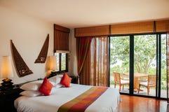 Thail?ndskt tropiskt hemtrevligt hotellsovrum - hem- garnering f?r asiatisk tappning royaltyfri bild