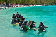 THAILAND Ö KORALL, MARS 19, 2018 - lär kinesiska turister för grupp att simma med dykapparaten Lagledareshower hur man använder a arkivfoto