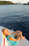 Thailand. Andaman sea. Beautiful girl. Thailand. Andaman sea. Similan islands. Calm blue sea, big stones and diving boat at a sunrise. Beautiful white-haired royalty free stock images