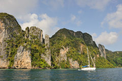 Thailand. Andaman sea. Phi Phi island. White yacht. Is at anchor near rocky coast Stock Photography