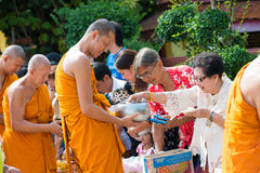 Thailand 13 Apr :: give alms to a Buddhist monk in Songkran Fest Royalty Free Stock Photo