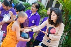 Thailand 13 April:: ge allmosa till en buddistisk munk i den Songkran festen Royaltyfri Bild