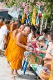Thailand 13 April:: ge allmosa till en buddistisk munk i den Songkran festen Arkivbild