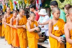 Thailand 13 April:: ge allmosa till en buddistisk munk i den Songkran festen Royaltyfri Foto
