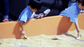 Thailand, Bangkok, 23 november 2015. Asian children play with sand in the playground. 3840x2160. Child two cute little girls build sand castle in the playground stock video