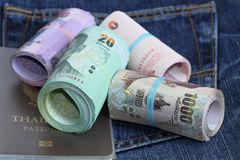 Thailand bank note. Roll of Thailand bank note and passport with jeans background Royalty Free Stock Images