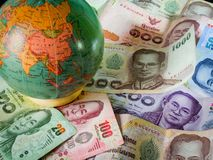 Thailand banknotes spread across table with globe. Multiple Thai banknotes on display with Globe of thailand royalty free stock photography