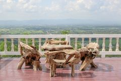 Old wooden table and old wooden chair. In the sunlight, over looking the sky, mountains and downtown Phrae Province Thailand stock images
