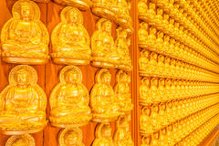 Thousand golden buddha sculpture on a wall at Wat  Stock Image