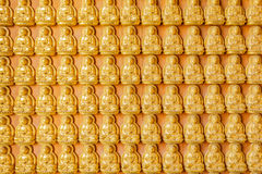 Thousand golden buddha sculpture on a wall at Wat  Stock Images