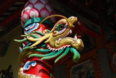 Thailand dragon. Temple in Thailand with wooden pillar with colourful dragon and lotus flower Stock Image