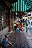 Thailand elderly woman sitting on ground. In China town Royalty Free Stock Images