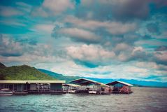 Thailand. Fisherman raft house in big lake with mountain and tree in the background in cloudy day , Floating houses in Kanchanabur Stock Image