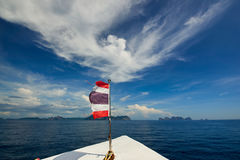 Thailand flag with boat sails to Koh Phi Phi island, Thailand Royalty Free Stock Photos